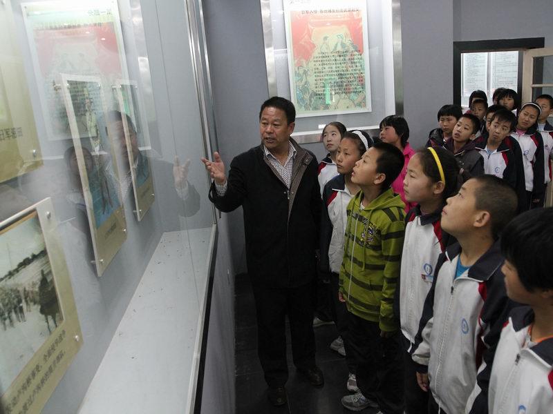 展板前,老师们教育学生要牢记先 前赴后继、为他人谋幸福的高尚品图片